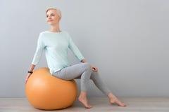 Donna che si siede sul fitball e che guarda da parte Immagine Stock Libera da Diritti