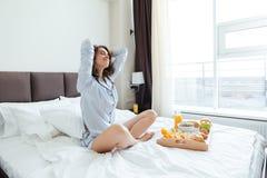 Donna che si siede sul letto che ha prima colazione ed allungamento Immagine Stock Libera da Diritti