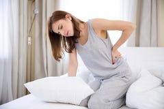Donna che si siede sul letto con dolore alla schiena Fotografia Stock