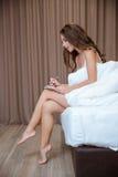 Donna che si siede sul letto con la penna ed il blocco note Fotografia Stock Libera da Diritti