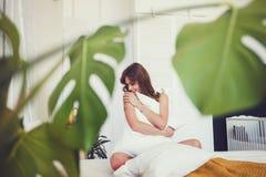 Donna che si siede sul letto e che abbraccia cuscino bianco immagine stock libera da diritti