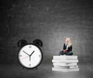 Donna che si siede sul mucchio dei libri, grande destra della sveglia Fotografia Stock