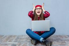 Donna che si siede sul pavimento con il computer portatile e che grida Immagine Stock