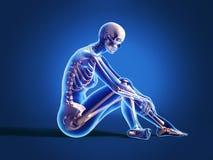 Donna che si siede sul pavimento, con lo scheletro dell'osso. Immagini Stock