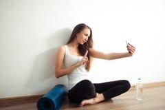 Donna che si siede sul pavimento e che fa selfie sullo smartphone nella palestra di forma fisica Fotografia Stock