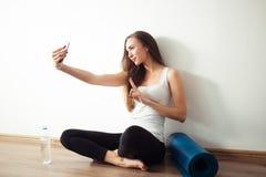 Donna che si siede sul pavimento e che fa selfie sullo smartphone nella palestra di forma fisica Fotografia Stock Libera da Diritti