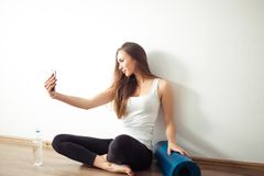 Donna che si siede sul pavimento e che fa selfie sullo smartphone nella palestra di forma fisica Immagine Stock