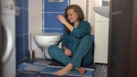 Donna che si siede sul pavimento nel test di gravidanza della tenuta del bagno con due bande archivi video