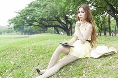Donna che si siede sul prato inglese Fotografia Stock Libera da Diritti