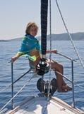 Donna che si siede sul radiatore anteriore dell'yacht immagine stock libera da diritti