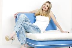 Donna che si siede sul sofà Immagine Stock