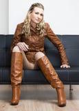 Donna che si siede sul sofà Immagini Stock Libere da Diritti