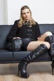 Donna che si siede sul sofà Fotografie Stock