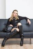 Donna che si siede sul sofà Fotografia Stock Libera da Diritti