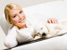 Donna che si siede sul sofà con il cucciolo di sonno fotografie stock