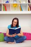 Donna che si siede sul sofà e che legge il libro Fotografia Stock