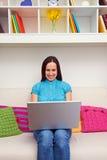 Donna che si siede sul sofà e che tiene il computer portatile Fotografia Stock