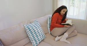 Donna che si siede sul sofà che legge un romanzo 4K 4k archivi video