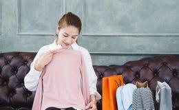 Donna che si siede sul sofà sta tenendo una camicia rosa e sta sorridendo immagine stock libera da diritti