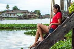 Donna che si siede sull'acqua di legno delle scale fotografia stock