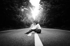 donna che si siede sull'automobile aspettante della strada Fotografie Stock