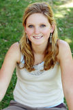 Donna che si siede sull'erba fotografie stock