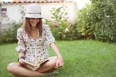donna che si siede sull'erba e che legge il libro Fotografia Stock Libera da Diritti