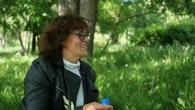 Donna che si siede sull'erba e sul sorridere Festa della famiglia nel parco stock footage