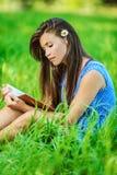 Donna che si siede sull'erba e sulla lettura Fotografie Stock