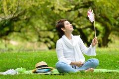 Donna che si siede sull'erba verde che gode della natura Fotografia Stock