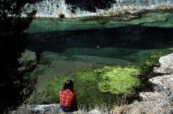 Donna che si siede sulla banca di un fiume Fotografie Stock Libere da Diritti