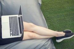 Donna che si siede sulla borsa di fagiolo e che per mezzo del computer portatile al giardino all'aperto dentro Fotografia Stock