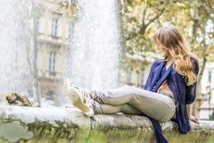 Donna che si siede sulla fontana fotografia stock
