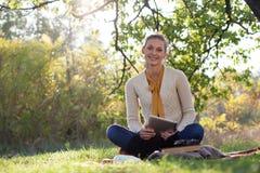 Donna che si siede sulla lettiera su erba verde fotografie stock