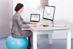 Donna che si siede sulla palla dei pilates facendo uso del computer Fotografie Stock