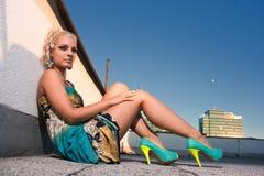 Donna che si siede sulla parete Fotografia Stock
