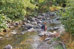 Donna che si siede sulla roccia del fiume della montagna in autunno Fotografia Stock Libera da Diritti