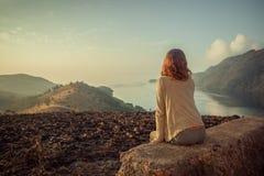Donna che si siede sulla roccia insolita all'alba Fotografia Stock Libera da Diritti