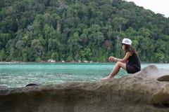 Donna che si siede sulla roccia la parte anteriore di lei ha il mare blu e parte anteriore verde Immagine Stock
