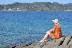 Donna che si siede sulla roccia vicino al mare Fotografia Stock