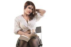 Donna che si siede sulla sedia con il libro Immagini Stock