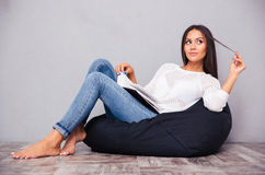 Donna che si siede sulla sedia della borsa con il libro Fotografia Stock