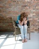 Donna che si siede sulla sedia nella depressione Fotografie Stock Libere da Diritti