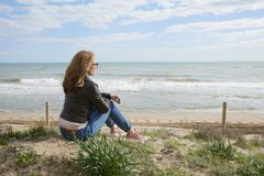 Donna che si siede sulla spiaggia Immagine Stock