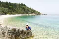 Donna che si siede sulla spiaggia immagine stock libera da diritti
