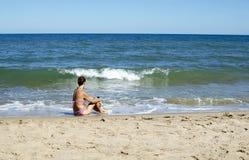 Donna che si siede sulla spiaggia Fotografia Stock