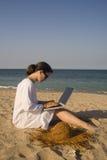 Donna che si siede sulla spiaggia con il computer portatile Fotografie Stock Libere da Diritti
