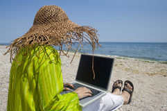 Donna che si siede sulla spiaggia con il computer portatile Immagini Stock