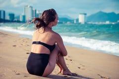 Donna che si siede sulla spiaggia in costume da bagno nero che gode delle vacanze estive che esaminano l'oceano Fotografia Stock