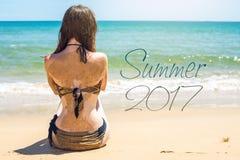 Donna che si siede sulla spiaggia sabbiosa e sugli sguardi fuori al mare Fotografie Stock